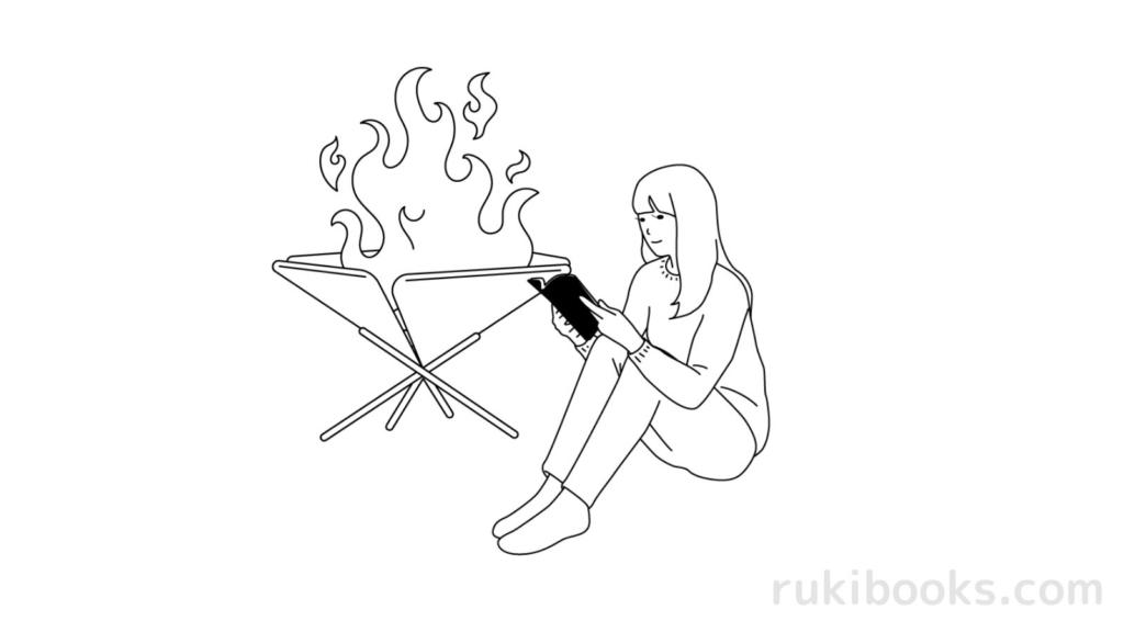 火の近くで本を読む女の人の画像